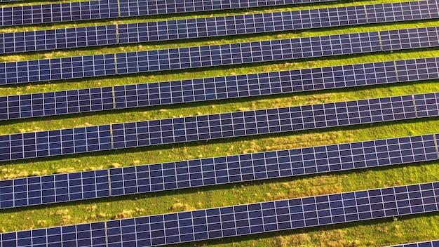 Luftdrohnenansichtsflug über solarkraftwerkspanels. luftaufnahme des solarparks. grüne energie, elektrische innovation. erneuerbare energie. industrieller solarenergiepark, der solarstrom produziert.