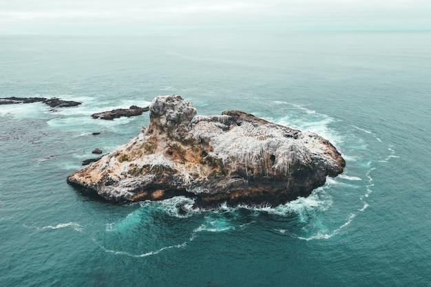 Luftdrohnenaufnahme einer kleinen felseninsel im blauen schönen ozean