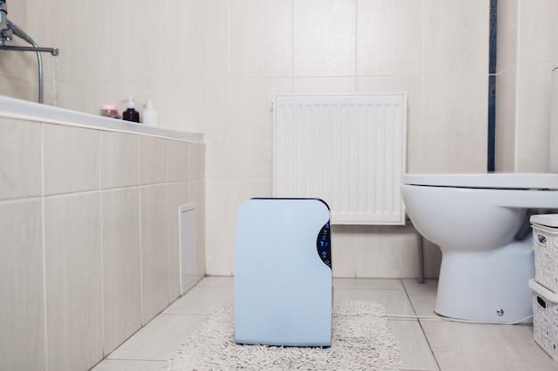 Luftentfeuchter mit touch-panel, feuchtigkeitsanzeige, uv-lampe, luftionisator, wasserbehälter arbeitet im badezimmer. lufttrockner