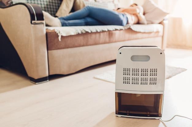 Luftentfeuchter mit touch-panel, feuchtigkeitsanzeige, uv-lampe, luftionisator, wasserbehälter arbeitet in der wohnung. nahansicht