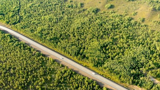 Luftflug über eine landstraße mit zwei autos, die sich auf der spur zwischen wald an einem sonnigen tag gegenüber fahren.