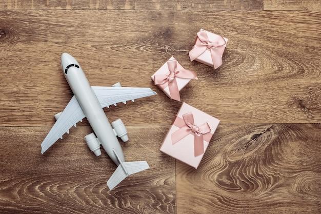 Luftfracht. flugzeugfigur und geschenkboxen auf dem boden. flach liegen.
