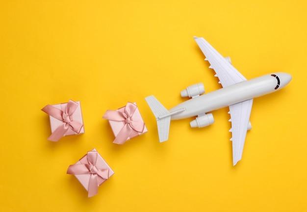 Luftfracht. flugzeugfigur und geschenkboxen auf gelb.