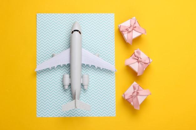 Luftfracht. flugzeugfigur und geschenkboxen auf gelbblauem pastell.