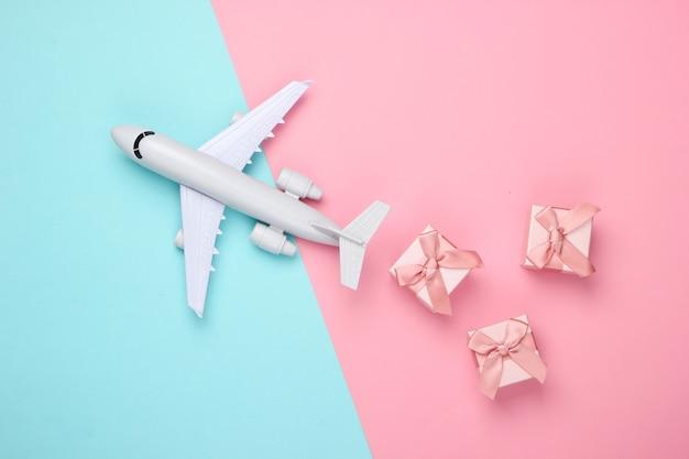 Luftfracht. flugzeugfigur und geschenkboxen auf rosa blauem pastell.