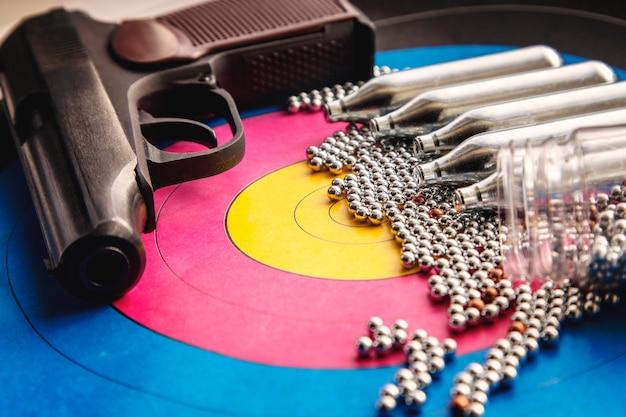 Luftgewehr, gasdosen und pellets auf dem hintergrund des ziels