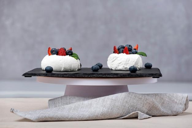 Luftiger baiserkuchen mit frischen blaubeeren und erdbeeren auf schwarzem tablett.