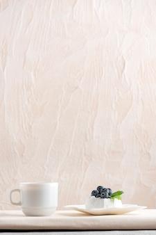 Luftiger kuchen mit frischen beeren auf untertasse und tasse kaffee. vertikaler rahmen, kopierraum.