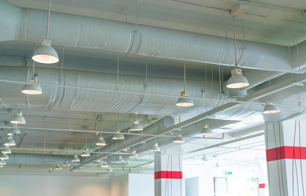Luftkanal, klimaanlagenrohr, kabelrohr und sprinkleranlage. luftstrom- und lüftungssystem. gebäudeinnenraum. deckenleuchte mit geöffnetem licht.