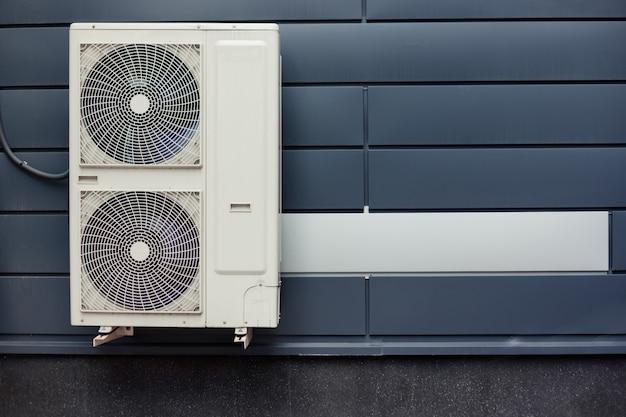 Luftkompressor-installation auf metallfliesenwand des modernen gebäudes