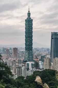Luftpanorama über im stadtzentrum gelegenem taipeh mit wolkenkratzer taipehs 101 mit bäumen auf berg im vordergrund in der dämmerung vom xiangshan-elefantenberg am abend.