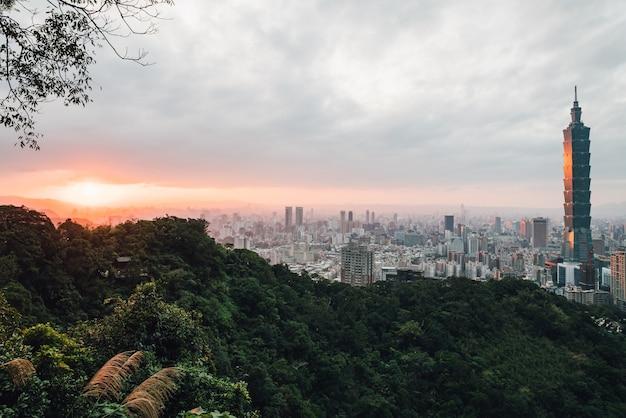 Luftpanorama über im stadtzentrum gelegenem taipeh mit wolkenkratzer taipehs 101 mit bäumen auf berg im vordergrund.