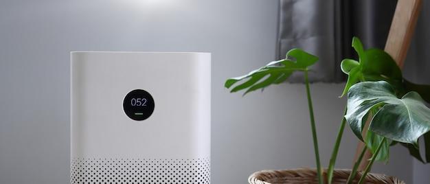 Luftreiniger mit digitalem monitorbildschirm im schlafzimmer zur anzeige von luftqualität und luftverschmutzung.