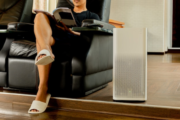 Luftreiniger mit mann, der buch im wohnzimmer liest.