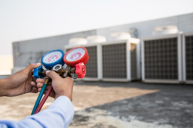 Luftreparaturmechaniker mit messgeräten zum befüllen von industrieklimageräten