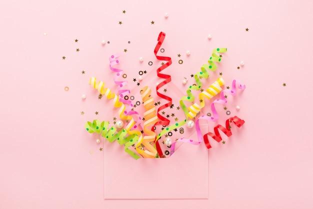 Luftschlangen und geöffneter umschlag auf rosa oberfläche
