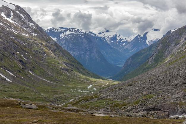 Luftsommeransicht der grünen schlucht in den bergen, die durch wolken in norwegen umgeben sind