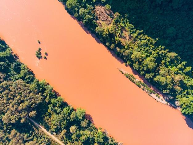 Luftspitze unten nam ou river nong khiaw muang ngoi laos, rotbraunes wasser, das wald durchfließt
