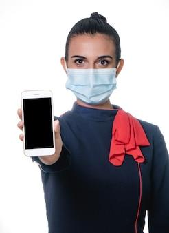 Luftverwalterin der jungen frau in der uniform, die gesichtsmaske trägt, um coronavirus-pandemie zu verhindern