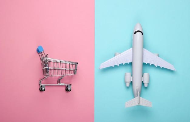 Luftzustellung, einkaufen, logistik. figur des einkaufswagens, flugzeug auf blauem rosa pastell.