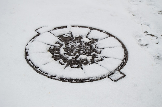 Luke bedeckt städtisches abwasser, das mit dem ersten schnee bedeckt ist