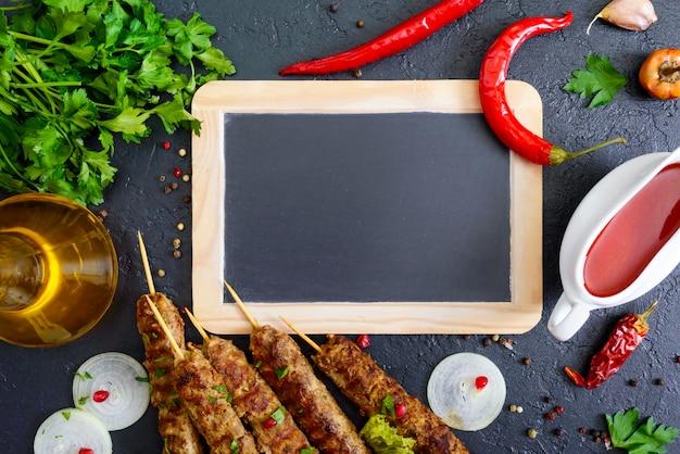 Lula kebab ist ein traditionelles arabisches gericht. fleischschaschlik auf holzspießen, würzige tomatensauce auf schwarzem hintergrund. freier platz zum schreiben auf die tafel in der mitte