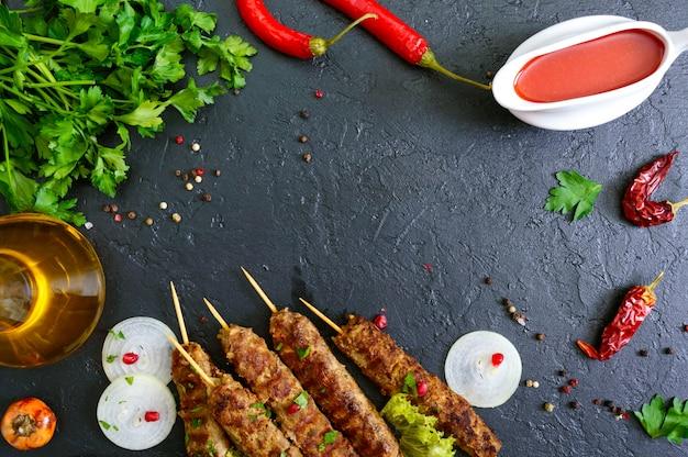Lula kebab ist ein traditionelles arabisches gericht. fleischschaschlik auf holzspießen, würzige tomatensauce auf schwarzem hintergrund.