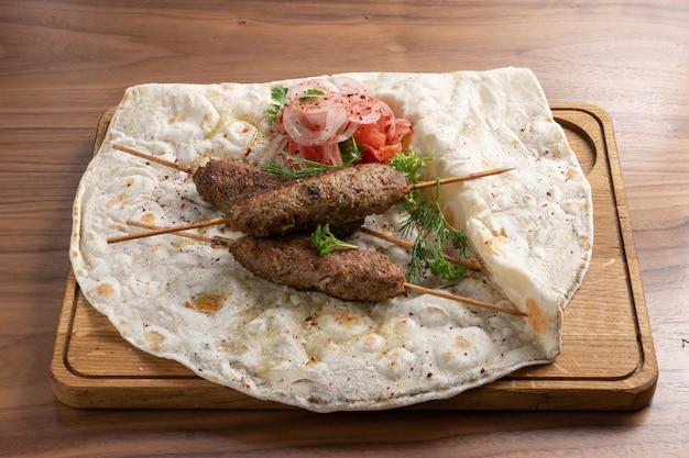 Lula kebab ist ein traditionelles orientalisches gericht aus hackfleisch auf fladenbrot mit gemüse und kräutern.