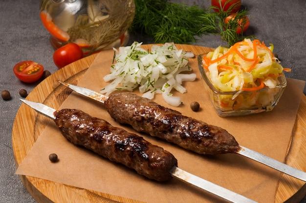 Lula-kebab mit eingelegten zwiebeln und kohlsalat