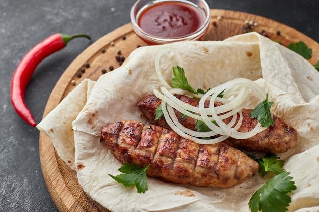 Lula kebab mit fladenbrot auf einem holzbrett