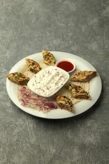 Lule-kebab in fladenbrot gewickelt, serviert mit joghurt und tomatensauce