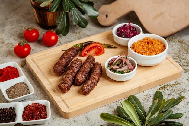 Lule kebab serviert mit bulgur bowl zwiebelsalat und rotkohlgurken