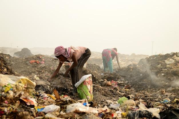 Lumpensammler suchen nach recycelbarem material im müllland und luftverschmutzung in indien
