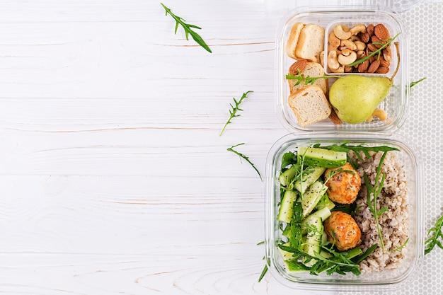 Lunchbox gefüllt mit haferflocken, gurkensalat und nüssen, brot, birne auf weißem holzhintergrund. lunchbox-abendessen. ansicht von oben, flach