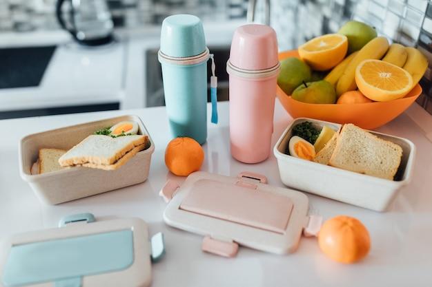 Lunchbox gefüllt mit sandwich in der nähe von zwei thermoskannen, frischen äpfeln und orangen, bananen vor weißem modernen küchentisch