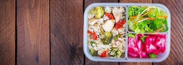 Lunchbox huhn, brokkoli, grüne erbsen, tomate mit reis und rotkohl