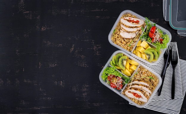 Lunchbox huhn, bulgur, microgreens, tomaten und obst. gesundes fitness-essen. wegbringen. brotdose. draufsicht