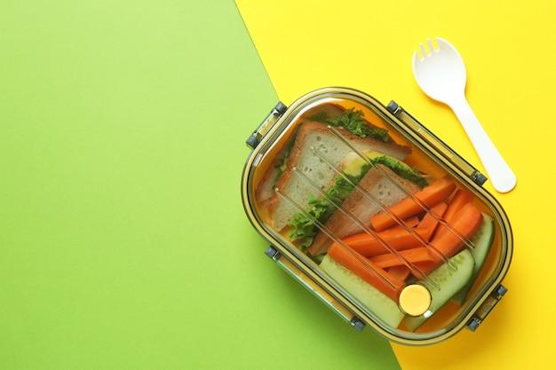 Lunchbox mit leckerem essen auf zweifarbigem hintergrund