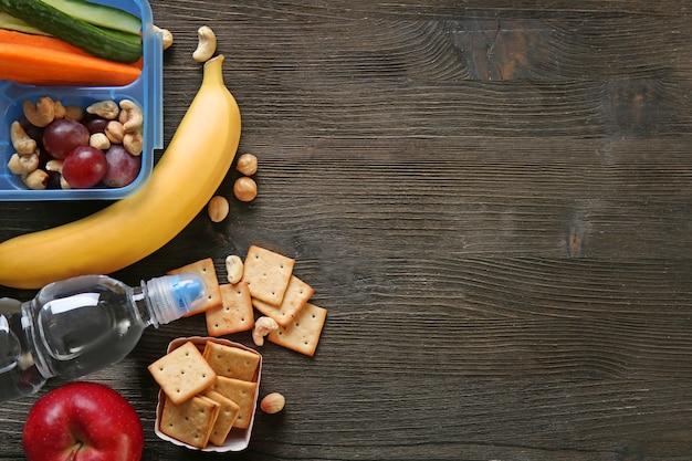 Lunchbox mit sandwich und verschiedenen produkten auf holzuntergrund