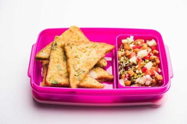 Lunchbox oder tiffin für indische kinder, beinhaltet brot omelett pakora mit tomatenketchup oder sprossen, selektiver fokus