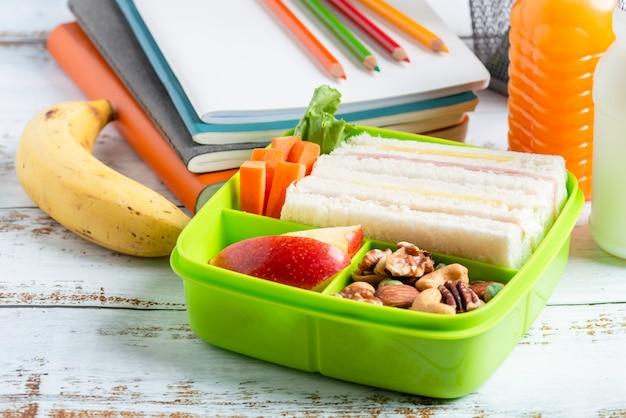 Lunchbox-set aus schinken-käse-sandwich mit karotten und gemischten nüssen, apfel in box, banane und orangensaft mit milch.