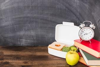 Lunchbox und Apfel in der Nähe von Büchern und Wecker