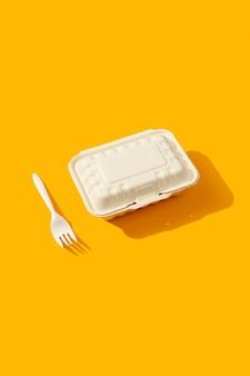 Lunchbox und gabel auf orangefarbenem tisch mit tiefem, langem schatten