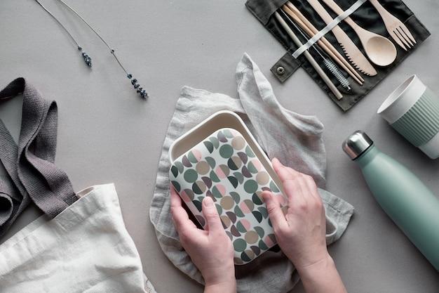 Lunchpaket ohne abfall, lunchbox zum mitnehmen auf baumwolltasche, organisator von bambusbesteck, bambus-lunchbox und wiederverwendbare tasse. nachhaltiger lebensstil, geometrische flache lage, draufsicht auf bastelpapier.