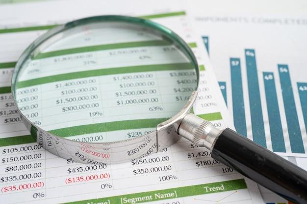 Lupe auf diagrammen millimeterpapier. finanzielle entwicklung, bankkonto, statistik, investitionsanalytische forschungsdatenwirtschaft, börsenhandel, geschäftsbüro-firmentagungskonzept.