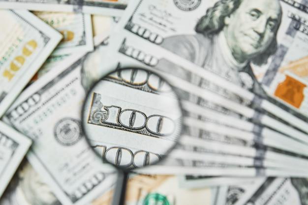 Lupe auf dollarnoten hintergrund. einhundert dollar usd banknoten. wirtschaftliche und finanzielle probleme