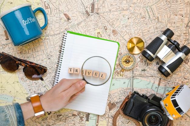 Lupe auf hölzernen würfeln nahe bei reiseelementen