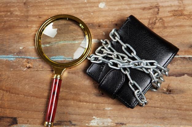 Lupe betrachtet eine geldbörse in ketten auf dem tisch