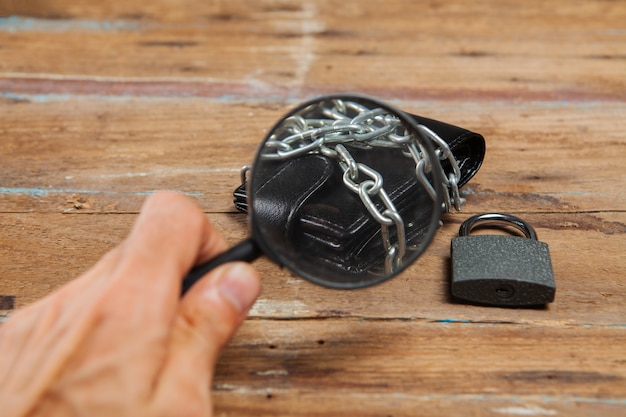 Lupe betrachtet eine geldbörse in ketten, verschlossen mit einem vorhängeschloss auf dem tisch
