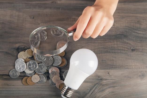 Lupe betrachtet münzen und eine glühbirne